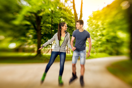 affectionate actions: young happy roller couple in park,  time for roller skates