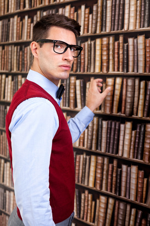 choose university: man take a book in library and looking at camera