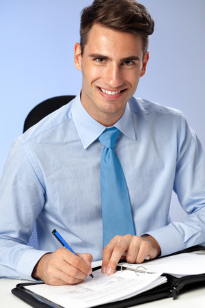 handsome  smiling business writing on papers at office desk photo