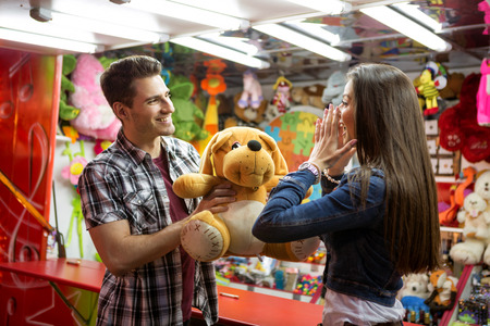 Man giving big teddy bear his girlfriend, he win in shooting game at amusement park