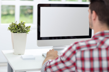 back screen:  Young man looking at computer screen, working in bright office