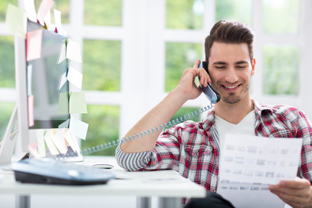 smiling young man working at his office   photo