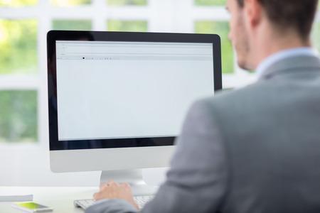usando computadora: Hombre de negocios sentado delante del monitor de vac�o, vista posterior Foto de archivo