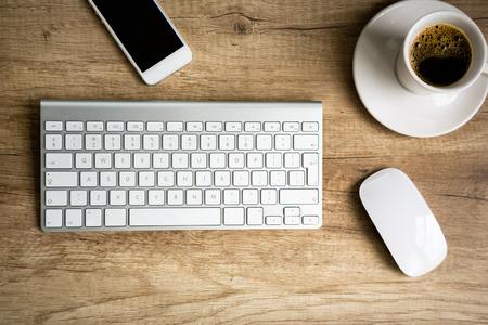 teclado: Espacio de trabajo moderno, el teclado y la taza de caf� sobre la mesa de madera Foto de archivo