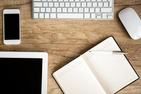 wooden desk: Notebook wit tablet op houten tafel, bovenaanzicht