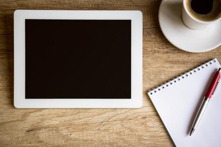 vista superior: Tablet con el cuaderno en la mesa de madera, vista desde arriba