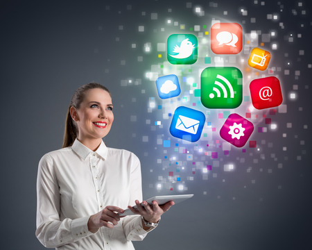 business woman tablet: internet - Young business woman with tablet and clouds of colorful media icons