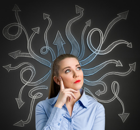 pointed arrows: Confused, young businesswoman with many arrows pointed in different directions Stock Photo