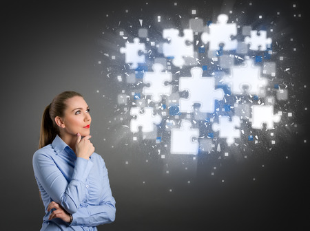 incomplete: Thinking businesswoman looking at clouds of shining puzzle pieces Stock Photo