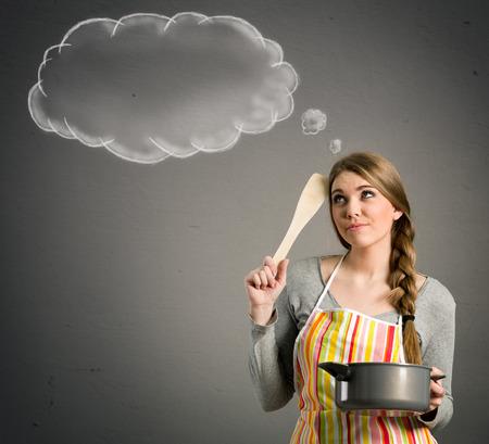 mujer pensando: hermosa joven ama de casa con los think vacío nubes, concepto - qué cocinar hoy?