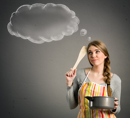 thinking woman: young beautiful housewife with empty think clouds, concept - What to cook today?