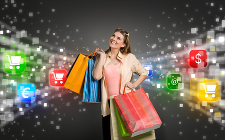 happy shopping woman surrounded by glow icons of e-commerce