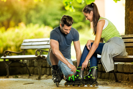 affectionate actions: Young man helping his girlfriends to put rollerblades