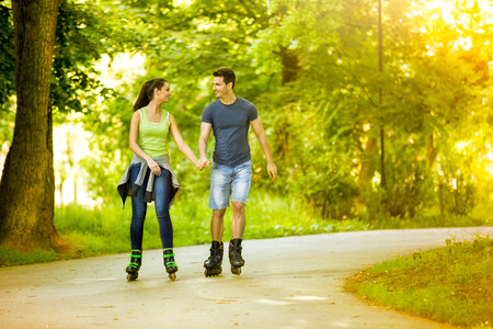 affectionate actions:  Young lovers in nature on rollerblades, enjoying in recreation Stock Photo