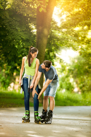 young boyfriend  helps his girlfriend to  driving rollerblades photo