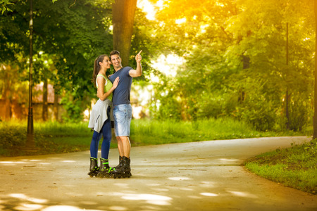 affectionate couple on rollerblades in park  photo