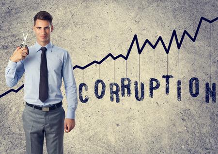 corrupcion: reducir la corrupción - hombre de negocios joven con tijeras de corrupción contra