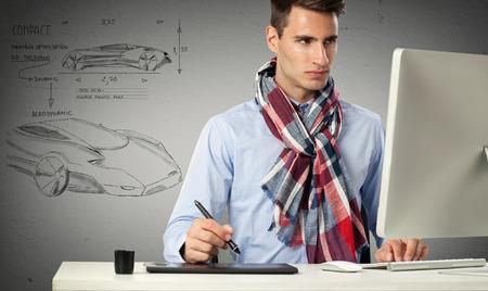 디자이너 컴퓨터 앞에 앉아 모델 자동차를 그립니다