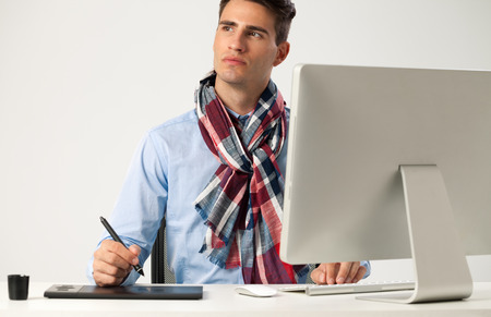 Graphic designer using graphics tablet to do his work at desk  photo