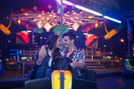 Affectionate couple sitting in bumper car at  amusement park photo
