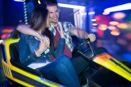 Young couple driving in a bumper car, dodgem ride photo