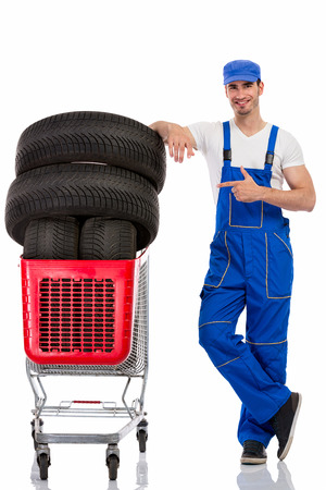 winter tyre: young  mechanic shopping  new tires, isolated over white