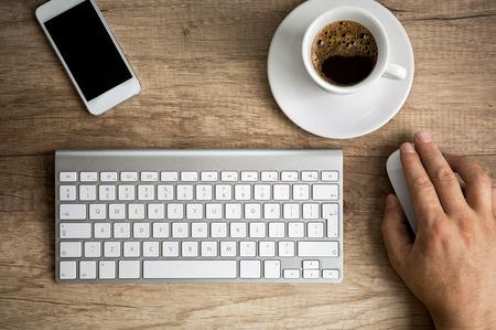 Muž ruku na počítačovou myš na dřevěném stole