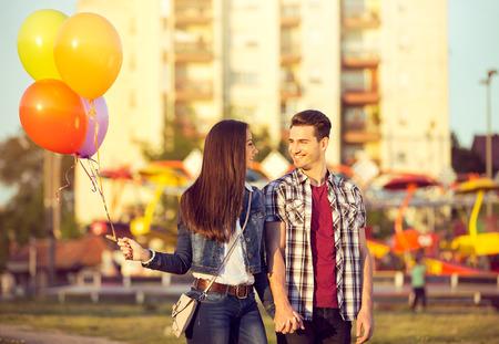 Happy couple walking through an amusement park Stock Photo