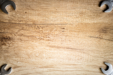 card board: wooden background with spanners screw