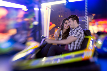 Happy couple enjoyment in attraction  at amusement park , ride bumper car - shoot with lens baby photo