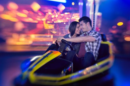 love couple in bumper car in amusement park- shoot with lens baby photo
