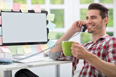 Smiling man drinking coffee at office and talking on phone photo