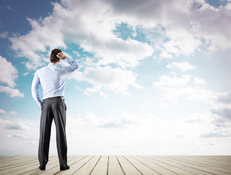 thought clouds: Back view of confident businessman looking at sky Stock Photo
