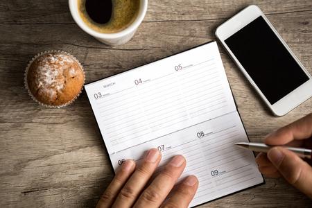 calendario: escritura de la mano masculina en la planificación de bloc de notas en el escritorio de madera