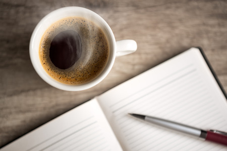office paper:  open empty notebook with coffee cup on wooden table