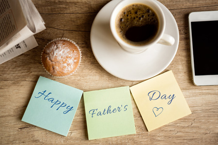 work desk with happy father's day on sticky paper photo