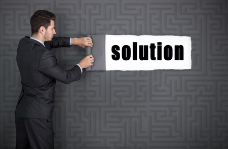 reveals: businessman tearing background with maze and reveals the solution to the problem Stock Photo