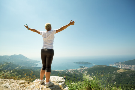 hands raised:  Woman with raised up hands enjoying sunny day,  mountains landscape
