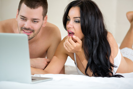 sexy couple in bed: Couple lying with laptop in bed and watching porn movie