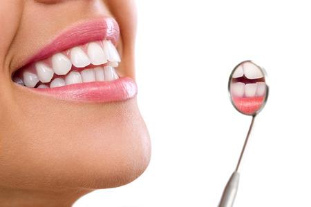 健康な女性の歯と歯科医口ミラー