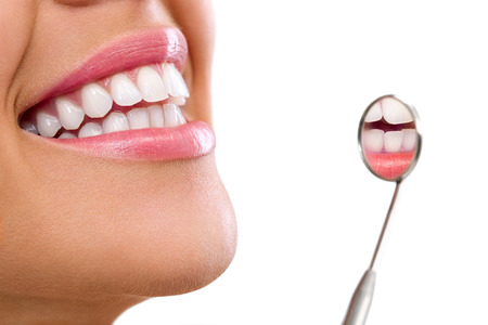 dentist and patient:  Healthy woman teeth and a dentist mouth mirror