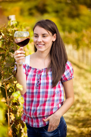 Young woman with glass of wine in the vineyard, tasting wine  photo