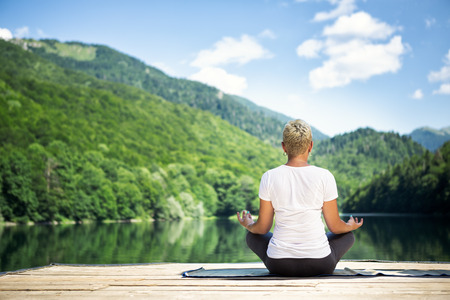jovem praticando meditação da ioga na natureza bonita, posição de lótus