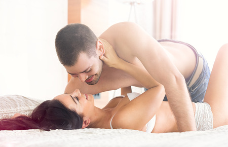 Sexy young couple lying and having foreplay on bed photo