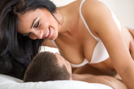 sexo pareja joven: Feliz pareja de jóvenes de Romancing de tener relaciones sexuales en la cama Foto de archivo
