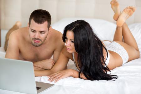 sex girl:  heterosexual couple watching movie on laptop computer in bedroom. Stock Photo