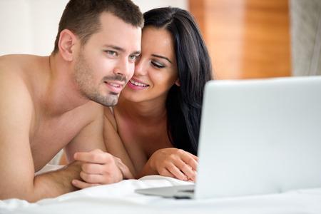 pornografia: Viendo la pel�cula porno sobre la computadora port�til en el dormitorio Pareja