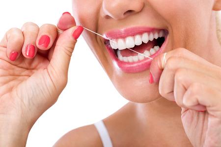 dientes: Ras Dental - mujer a usar seda dental sonriente Foto de archivo