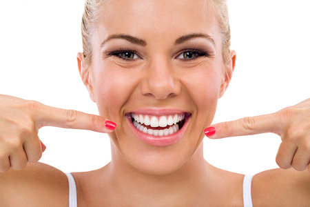 Smiling woman pointing in her perfect teeth , isolated over white