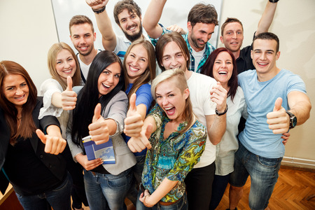 thumps up:  Happy group of students with thumbs up